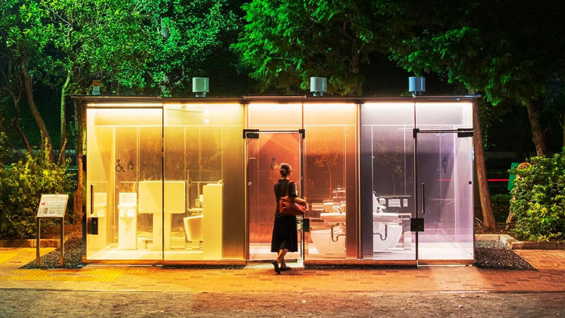 Three transparent toilets, lit up from within yellow, orange and lilac with a woman entering the centre toilet