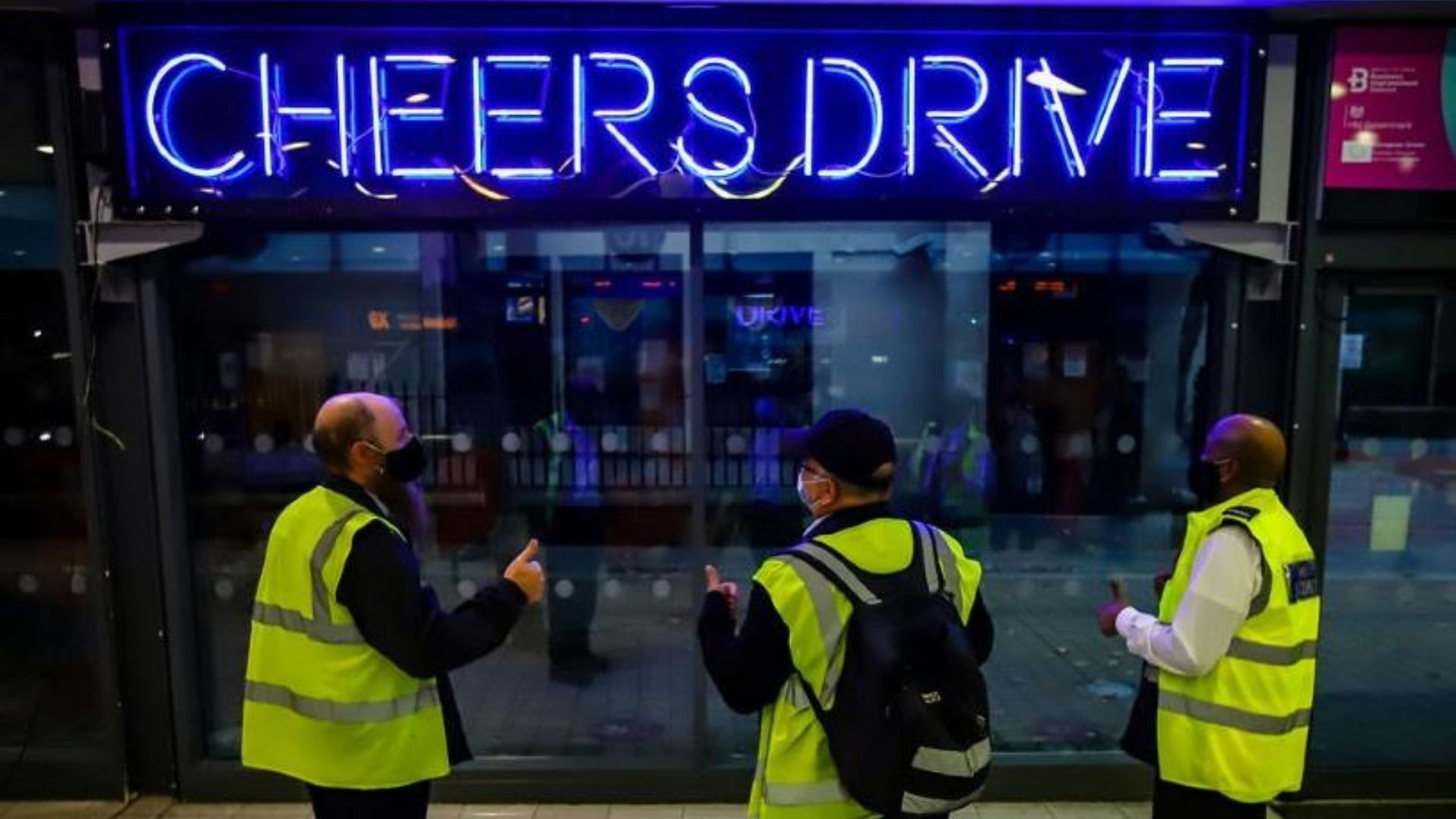Image of illuminated 'Cheers Drive' sign in Bristol Bus Station with three bus drivers looking at it