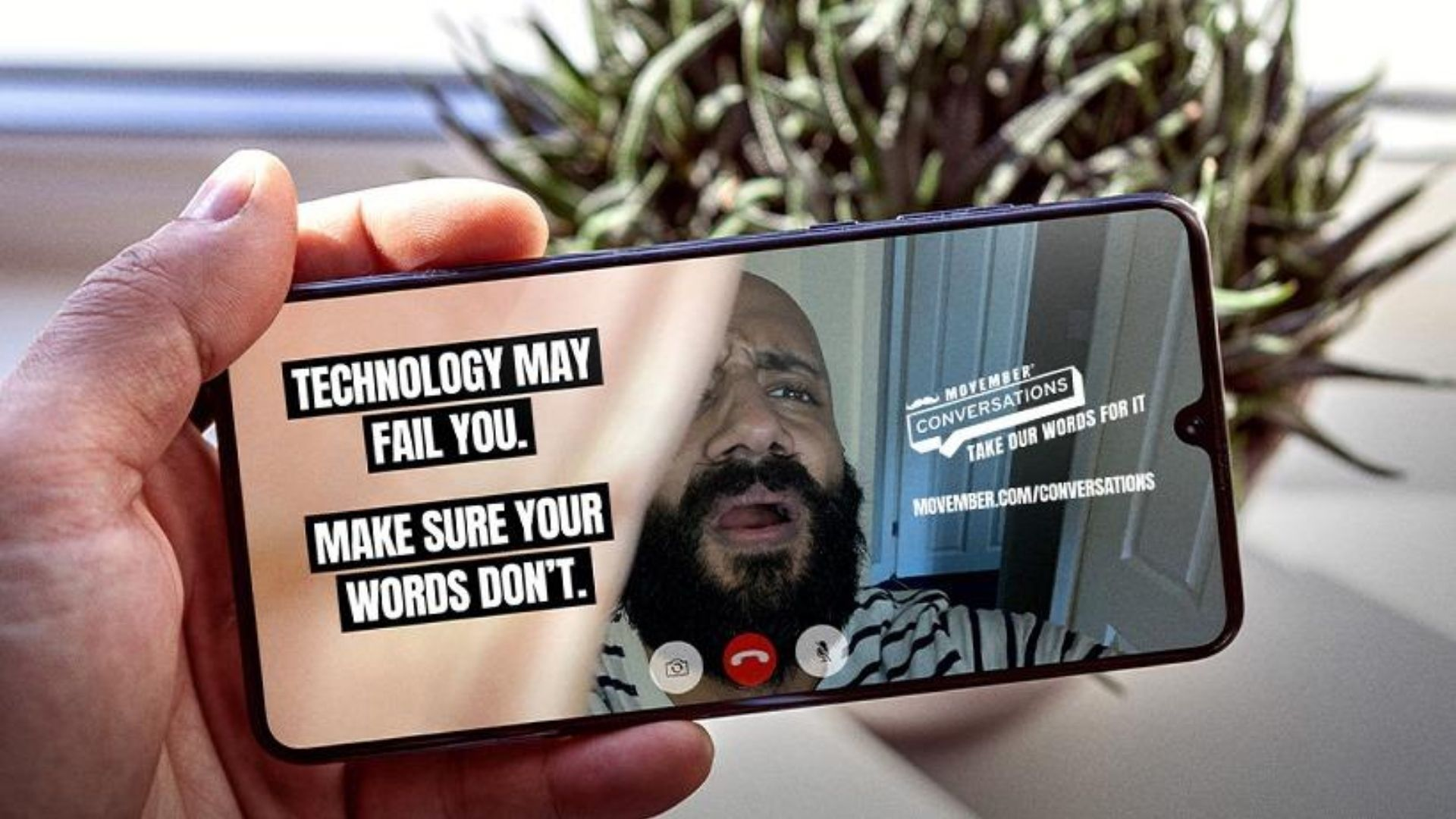 Image of IPhone held in man's  left hand. On the screen of the IPhone is a bearded man looking dismayed and text reading 'Technology may fail you. Make sure your words don't.'