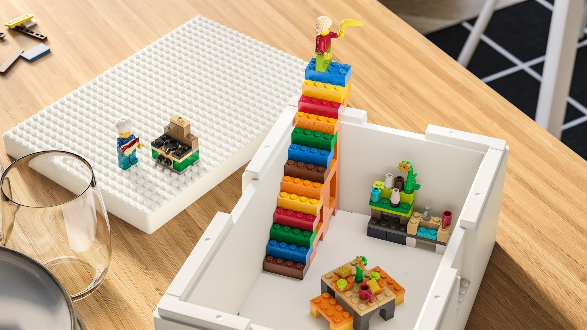 Image of IKEA's collaboration with LEGO. A white box containing multicoloured LEGO blocks and men, on a wooden table with a glass on the left hand side.