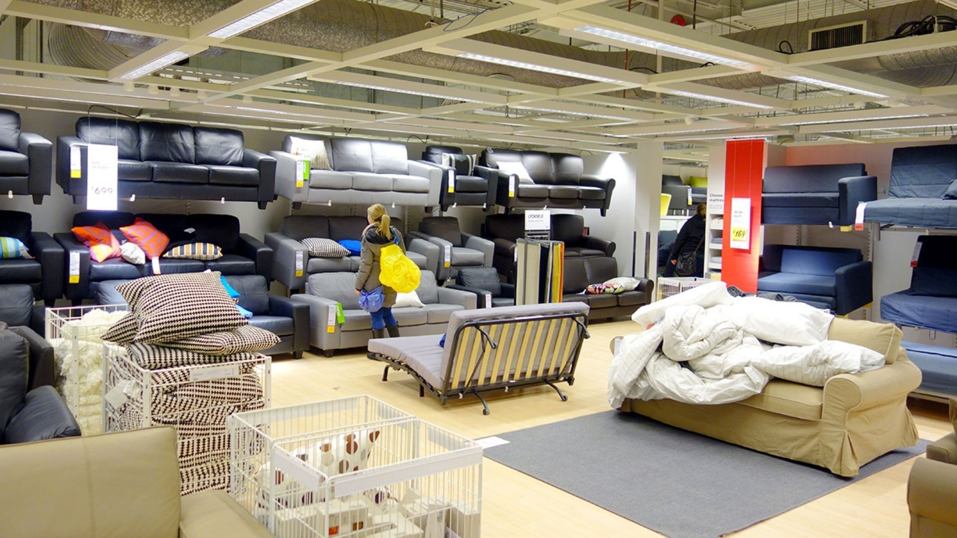 People browsing in a large room filled with a variety of sofas