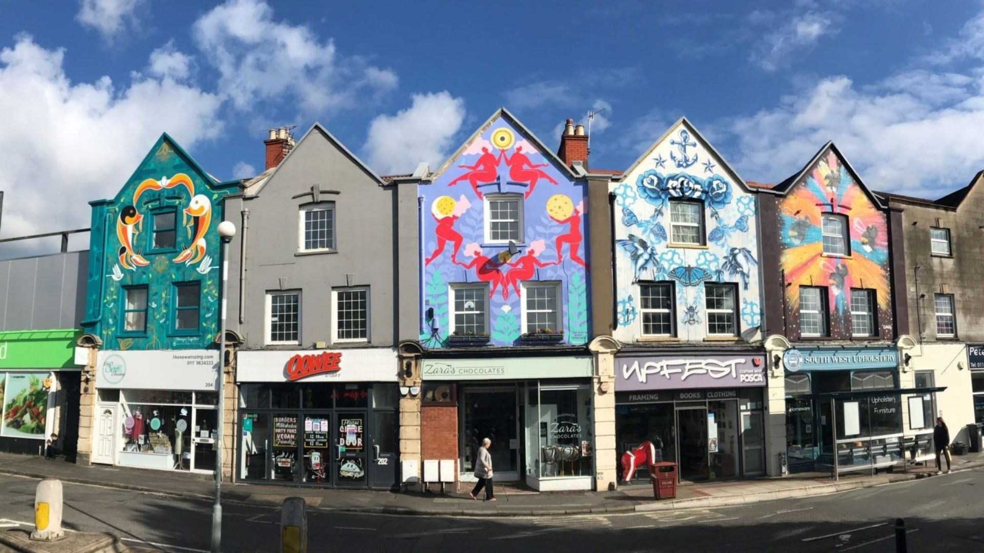 Image of five shop fronts on North Street in Bedminster, Bristol with colourful murals painted on them