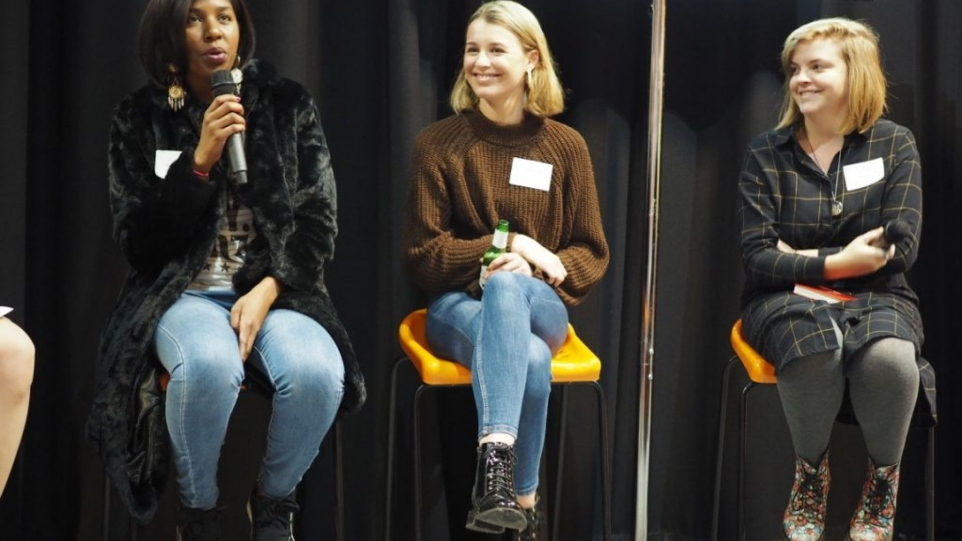 Three women sat on high yellow chairs holding microphones.