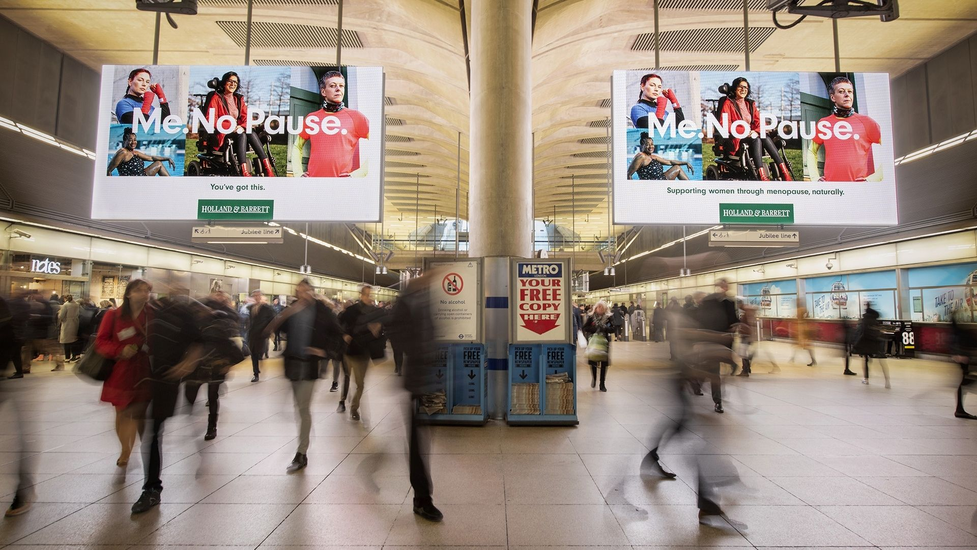 Image of people walking in London Underground tube station with Holland & Barrett adverts hanging from the ceiling.