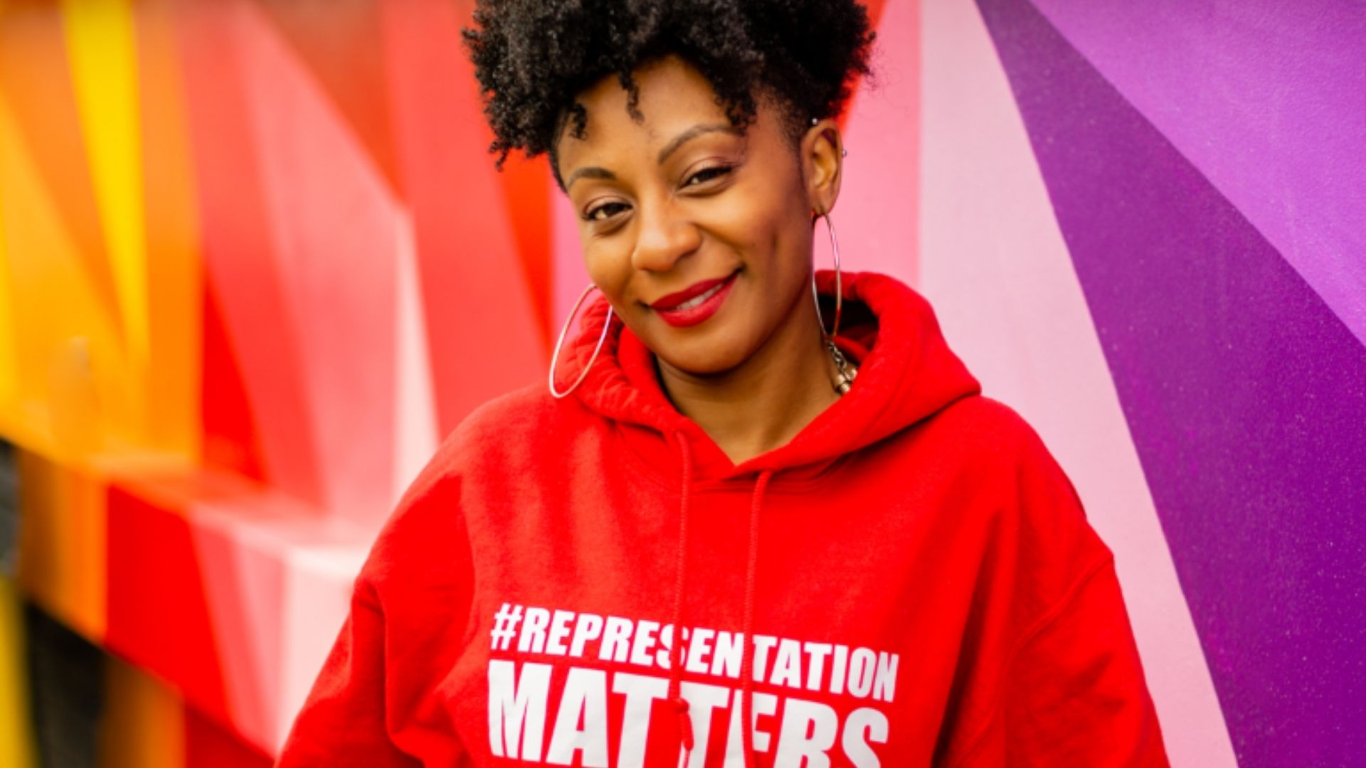 Image of Aisha Thomas, founder of 'Beyond the 26,' wearing a red hoodie that reads 'Representation Matters.'