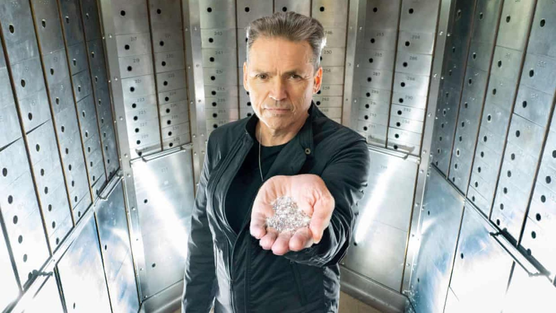 Dale Vince holding a handful of 'sky diamonds' created using a 'sky mining facility' to extract carbon from the atmosphere, with wind and sun providing the energy, as well as using rain water.
