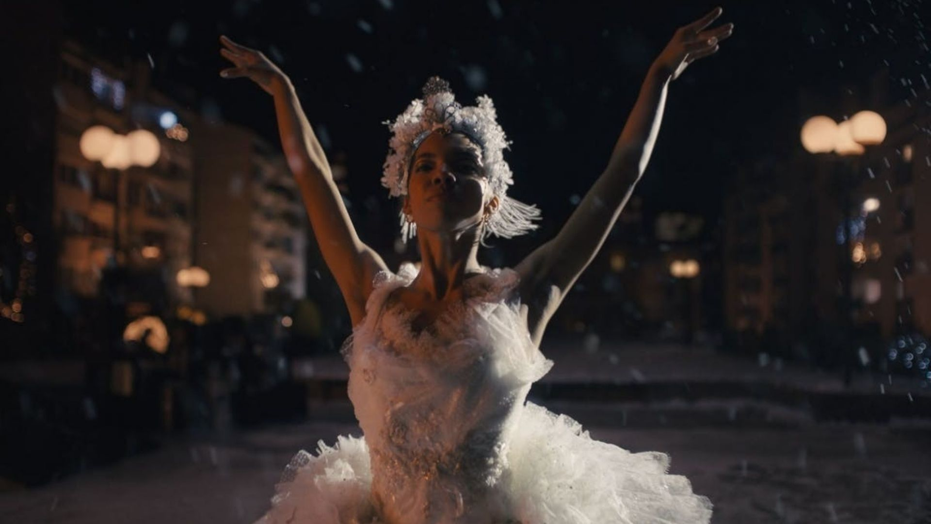 Black female ballet dancer in white dress and headdress with both of her arms raised.