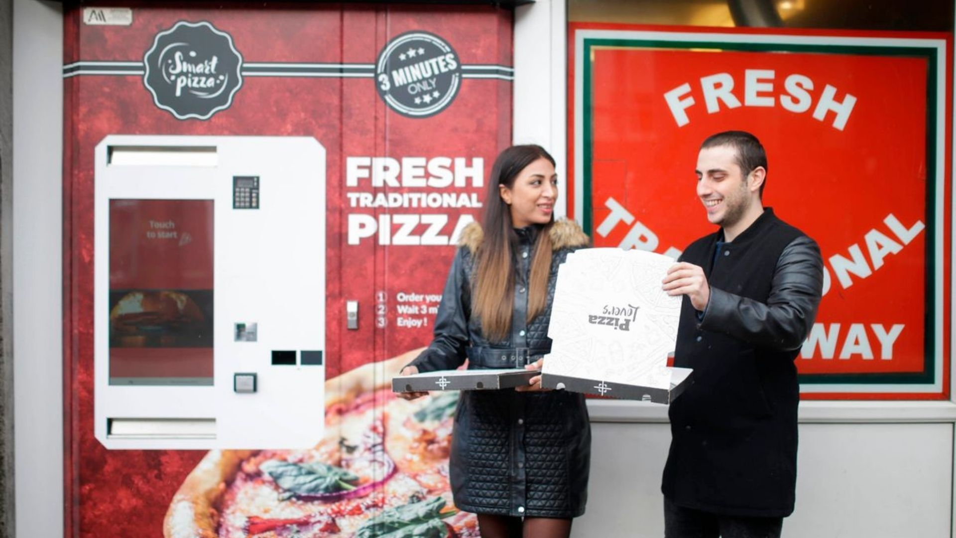 White woman and man using the UK's first pizza vending machine in Bedminster, South Bristol